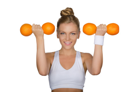 Beautiful woman with dumbbells of oranges isolated on white photo