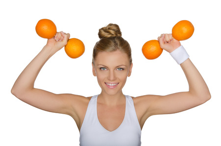 Beautiful woman with dumbbells from ripe oranges isolated on white photo