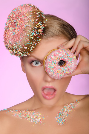 unexpectedness: surprised woman with donut on head and in front of eye on pink background