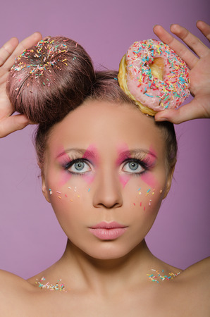 beautiful woman with two donuts on head on pink background photo