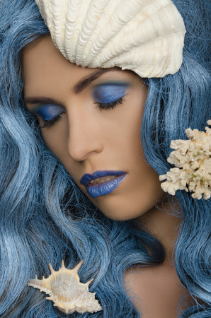 adult mermaid: woman with blue hair and seashells with eyes closed Stock Photo