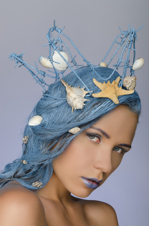 young beautiful woman with blue hair, crown and shells photo