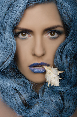 adult mermaid: Beautiful woman with blue hair and seashells looking at camera