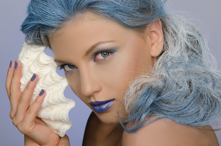 adult mermaid: charming woman with blue hair and seashells looking at camera