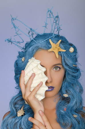Portrait of beautiful woman with blue hair, shells and crown photo