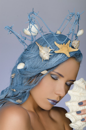 beautiful woman with blue hair, crown and shells photo