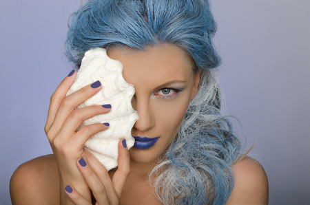 adult mermaid: charming  beautiful woman with blue hair and shell of person Stock Photo