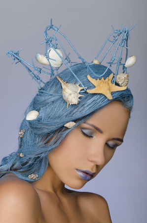 young attractive woman with blue hair, crown and shells photo