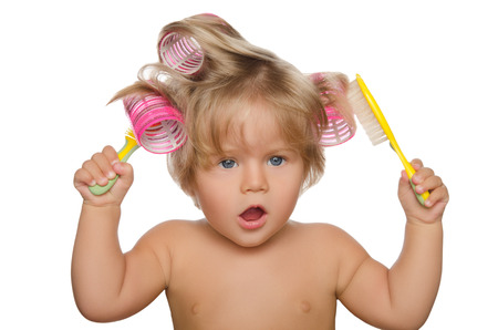horizontal haircut: Little beautiful kid with hair curlers and comb isolated on white Stock Photo