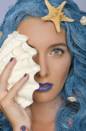 frizz: Portrait of beautiful woman with blue hair, shells and open eyes