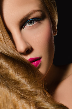 frizz: Portrait of blonde girl with beautiful hair on dark background