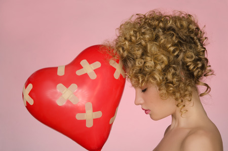 disillusionment: hurt woman with ball in shape of heart on pink background