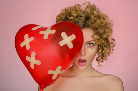 disillusionment: hurt young woman with ball in shape of heart on pink background Stock Photo