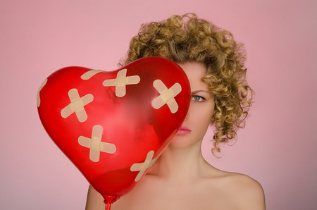 disillusionment: upset woman with ball in shape of heart on pink background Stock Photo
