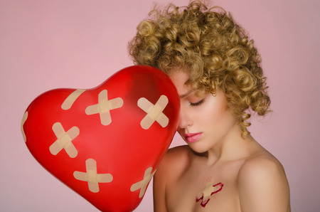 disillusionment: Unhappy young woman with patches on the body and balloon