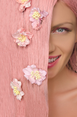 emote: Beautiful woman with pink hair and flowers on them looking at camera