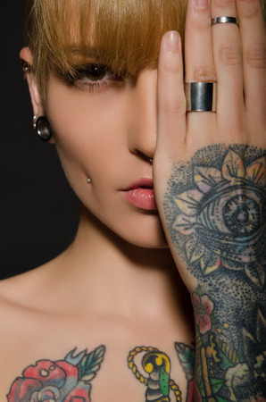 tatoo: Young blonde with a tattoo on body, dark background