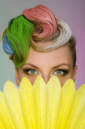 frizz: Portrait of charming woman with colorful makeup on colored background Stock Photo
