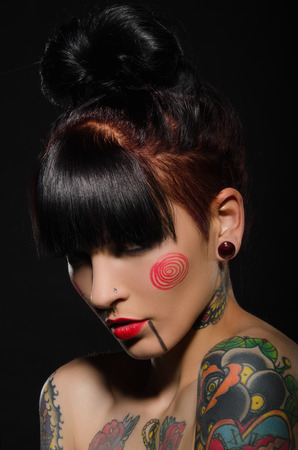 Young brunette with a tattoo on body, dark background