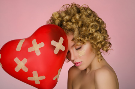 disillusionment: Balloon in shape of heart and hurt young woman on pink background