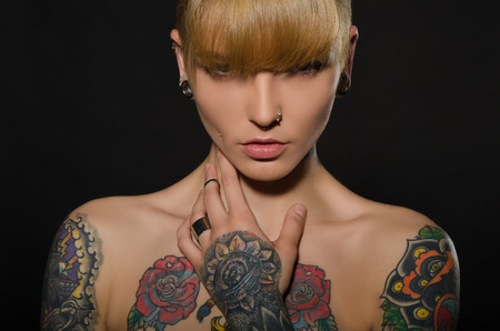 body piercing: Beautiful blonde with a tattoo on body, dark background
