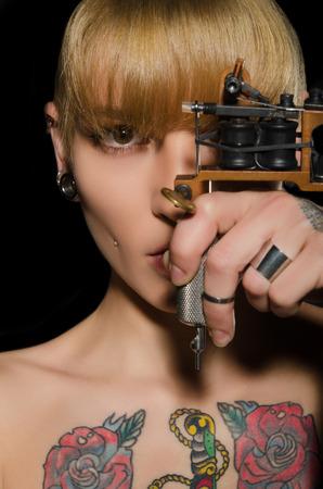 タトゥー マシン、暗い背景を持つ美しい女性に入れ墨