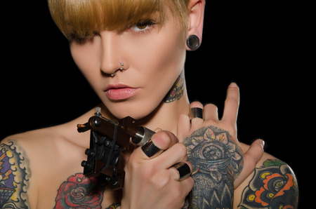 body piercing: tattooed charming woman with tattoo machine, dark background