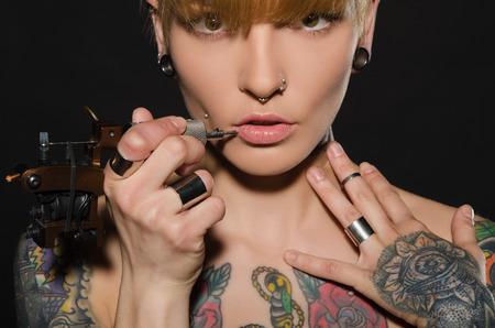 tatoo: charming blonde with tattoo machine and for them, dark background Stock Photo
