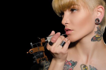 charming blonde makes herself tattoo, dark background 스톡 콘텐츠