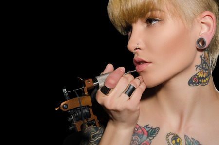 charming blonde makes herself tattoo, dark background Standard-Bild