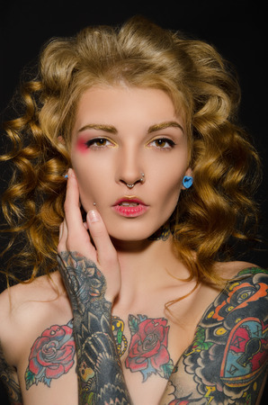 Charming blonde with a tattoo on body, dark background Standard-Bild