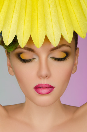 frizz: Beautiful woman with yellow paper on colorful background