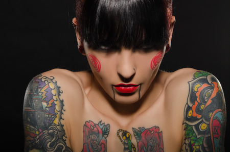 brunets: portrait of beautiful tattooed women on dark background