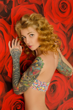 frizz: charming tattooed woman in background with red flowers Stock Photo