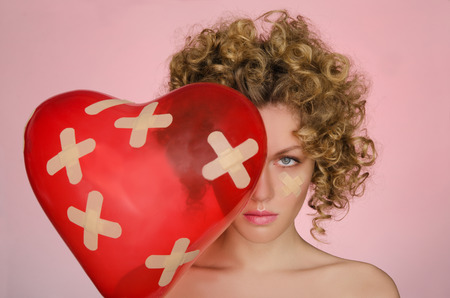 disillusionment: upset young woman with ball in shape of heart on pink background Stock Photo