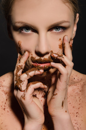 beautiful woman with chocolate on her face on dark background Imagens