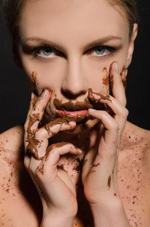Schöne Frau mit Schokolade auf ihrem Gesicht auf dunklem Hintergrund Standard-Bild - 39588692