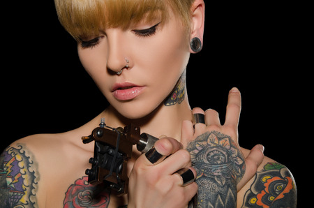 tattoo drawings: tattooed young woman with tattoo machine, dark background