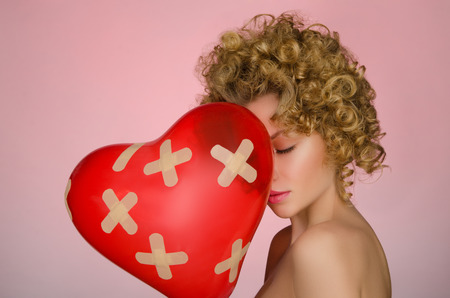 disillusionment: Unhappy young woman with ball in shape of heart on pink background