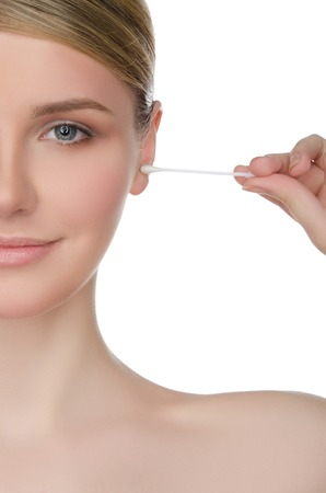 portrait of woman brushing her ear with cotton swab isolated on white