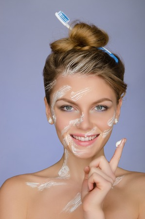 signify: woman in toothpaste on body and on your finger on blue background