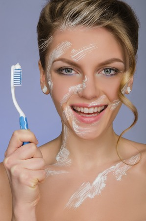 emote: charming woman with toothbrush and toothpaste on a blue background Stock Photo