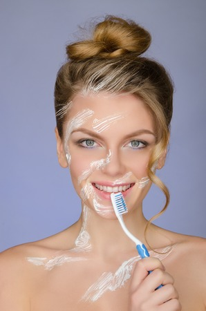 signify: smiling woman with toothbrush and toothpaste on a blue background