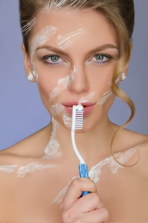 emote: woman with toothbrush and toothpaste on body on blue background