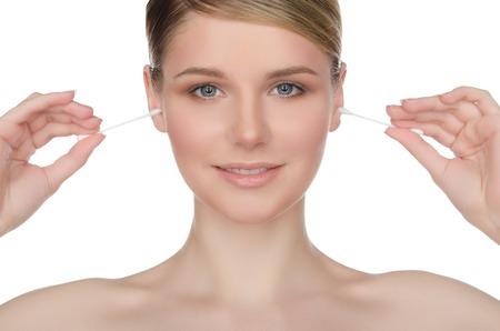oreja: hermosa mujer limpia los o�dos con bastoncillos de algod�n aislados en blanco Foto de archivo