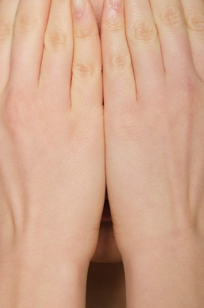 face covered: womans face covered by hand shot in studio Stock Photo