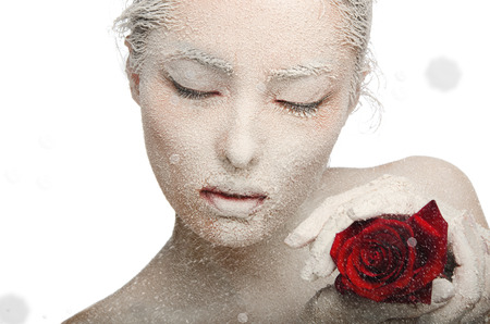 Frozen woman in snow and with rose in his hands Isolated on white
