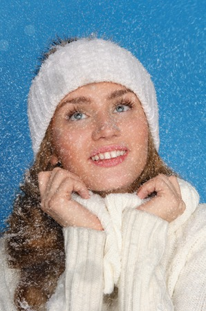 pleasantness: beautiful woman in winter clothes with snow on blue background