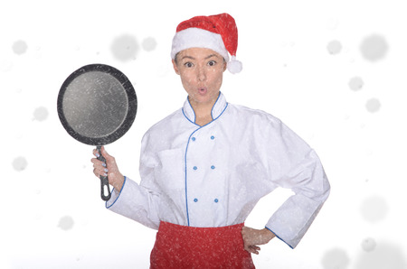 unexpectedness: surprised asian chef with frying pan and Christmas hat in falling snow