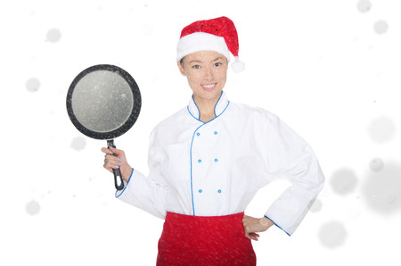 emote: smiling asian chef with frying pan and Christmas hat in falling snow Stock Photo